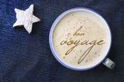 Cup of cappuccino coffee with foam in the form of words in French bon voyage on blue jeans, denim background. White wooden star. Royalty Free Stock Photo