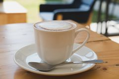 Cup of cappuccino coffee, hot mocha drink with cream on wood tab Royalty Free Stock Image