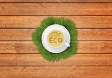 Cup of cappuccino coffee with image ECO symbol on wooden surface. Stock Photo