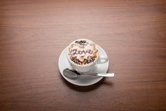 Cup of cappuccino coffee. Isolated on wooden background Royalty Free Stock Images