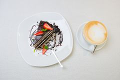 A cup of cappuccino coffee with slice of chocolate cake with strawberry stock photo