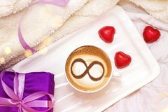 Coffee cup concept infinity symbol. A cup of cappuccino coffee with a symbol of the symbol of infinity on milk foam stock image