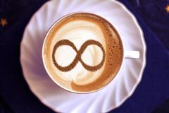 Coffee cup concept infinity symbol. A cup of cappuccino coffee with a symbol of the symbol of infinity on milk foam royalty free stock photography
