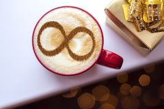Coffee cup concept infinity symbol. A cup of cappuccino coffee with a symbol of the symbol of infinity on milk foam royalty free stock photos