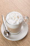 Cup of cappuccino coffee on wooden background. Cup of cappuccino coffee with marshmallow on wooden background Stock Photos