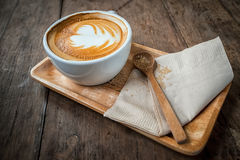 Cup of cappuccino coffee on wooden plate and brown sugar Royalty Free Stock Photo