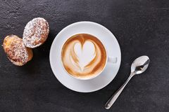 Cup of cappuccino with cookies. Top view of cup of creamy cappuccino with the shape of a heart, on dark stone background, with sweets and icing sugar stock photography
