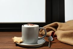 Cup of cappuccino with cookies on windowsill, space for text. Winter drink. Cup of cappuccino with cookies on windowsill indoors, space for text. Winter drink royalty free stock photos