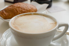 The cup of cappuccino with croissant in the background. Royalty Free Stock Photography
