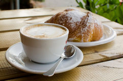 The cup of cappuccino with croissant in the background Royalty Free Stock Images
