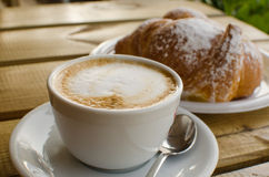 The cup of cappuccino with croissant in the background Stock Photos
