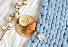 Cup with cappuccino, croissant, blue pastel giant plaid royalty free stock photo
