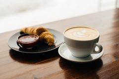 Cup of cappuccino and croissant with jam stock images