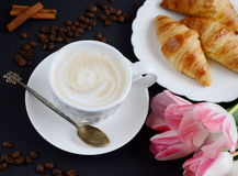 Cup of cappuccino and croissants with pink tulips on the table Stock Photography