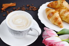 Cup of cappuccino and croissants with pink tulips on the table Stock Images