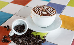A cup of cappuccino. Is decorated with spider web and coffee bean on the floor Royalty Free Stock Images