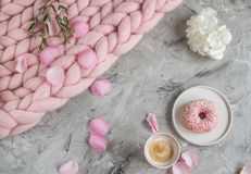 Cup with cappuccino, doughnut, pink pastel giant blanket, flowers. Bedroom, morning concept royalty free stock image