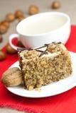 Cup Cappuccino, ein Stück des Kuchens mit Muttern Lizenzfreie Stockfotos