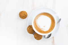 Cup of cappuccino and flavored cookies on white wooden table Royalty Free Stock Photography