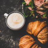 Cup of cappuccino, fresh croissants and pink flowers, square crop stock photography