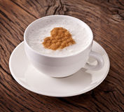 Cup of cappuccino with ground cinnamon in the form of heart. Stock Photo