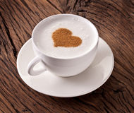 Cup of cappuccino with ground cinnamon in the form of heart. Royalty Free Stock Photography