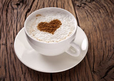 Cup of cappuccino with ground cinnamon in the form of heart. Stock Photography