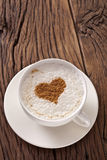 Cup of cappuccino with ground cinnamon in the form of heart. Stock Photos