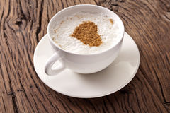 Cup of cappuccino with ground cinnamon in the form of heart. Royalty Free Stock Photos