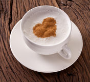 Cup of cappuccino with ground cinnamon in the form of heart. Stock Images