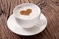 Cup of cappuccino with ground cinnamon in the form of heart. Royalty Free Stock Images
