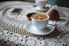Cup of cappuccino with ground cinnamon on table Royalty Free Stock Image