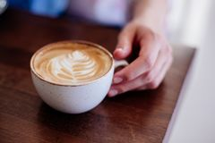 Cup of cappuccino in hand. Close up of beautiful female hand holding big white cup of cappuccino coffee Stock Photo