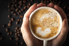 Cup of cappuccino in the hand Stock Image