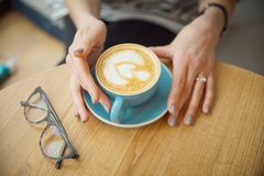 A cup of cappuccino in the hands of a girl. morning with coffee. coffee house stock image