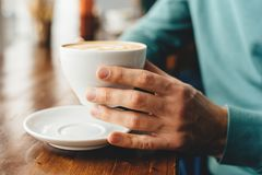 The cup of cappuccino in hands stock photos