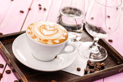 Cup of cappuccino with heart foam, set of cup of coffee with coffee beans on pink wooden background, drink hot product photography Stock Photos