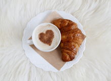 Cup of cappuccino with heart pattern of cinnamon and croissant stock image
