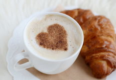 Cup of cappuccino with heart pattern of cinnamon and croissant Royalty Free Stock Photo