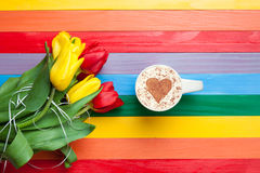 Cup of cappuccino with heart shape and bouquet of tulips. On multicolor background Stock Photos