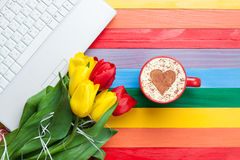 Cup of cappuccino with heart shape and computer Royalty Free Stock Photos