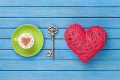 Cup of Cappuccino with heart shape symbol, key and toy Royalty Free Stock Photography