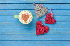 Cup of Cappuccino with heart shape symbol and toys Stock Images