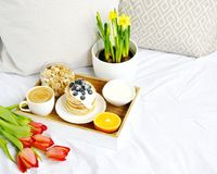 Cup with Cappuccino and Homemade Pancakes Sour Cream Berries Granola Orange Healthy Breakfast. Morning Concept Woman`s Day Flowers Tulips Daffodils Stock Photo