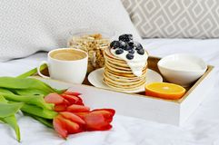Cup with Cappuccino and Homemade Pancakes Sour Cream Berries Granola Orange Healthy Breakfast. Morning Concept Woman`s Day Flowers Tulips Daffodils Stock Image