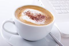 Cup of cappuccino with laptop Stock Image