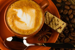 Cup of cappuccino, milk-chocolate wafer and coffee beans Royalty Free Stock Photos