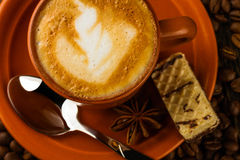 Cup of cappuccino, milk-chocolate wafer and coffee beans. Ceramic cup of cappuccino, milk-chocolate wafer and coffee beans on wooden background Stock Image