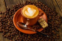 Cup of cappuccino, milk-chocolate wafer and coffee beans. Ceramic cup of cappuccino, milk-chocolate wafer and coffee beans on wooden background Royalty Free Stock Photos