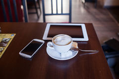 Cup of Cappuccino and mobile phone and tablet pc on wooden table Stock Photo